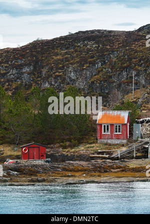 Old Norwegian red wooden houses on rocky coast - Stock Photo