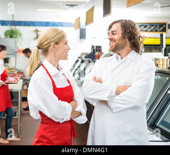 Happy Butchers Looking At Each Other In Store - Stock Photo