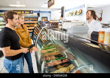 Salesman Attending Customers At Butcher's Shop - Stock Photo