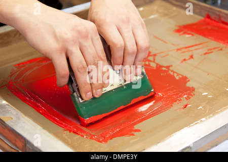 red color is printing on t-shirt with hands pressure - Stock Photo