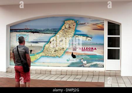 Man looking at Fuerteventura map on a wall, Caleta de Fuste, Fuerteventura, Canary Islands. - Stock Photo