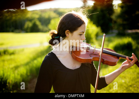Profile in artistry: pretty young brunette woman strikes just the right note on her antique italian violin; oh, - Stock Photo
