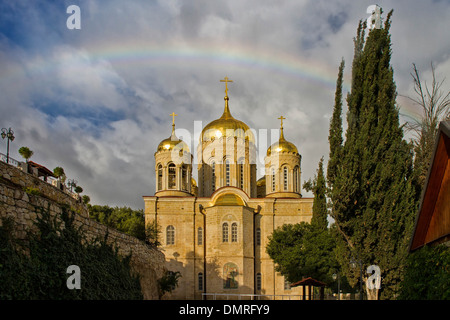 A rainbow breaks over the golden domes of Gornensky monastery of the Russian Ecclesiastical Mission in Jerusalem. - Stock Photo