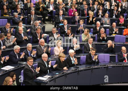 Berlin, Germany. 17th Dec, 2013. German Chancellor Angela Merkel (CDU, 1st Row, 3rd L) sits between the chairman of the CDU/CSU parliamentary group leader Volker Kauder and CSU regional faction leader Gerda Hasselfeldt at the German 'Bundestag' parliament in Berlin, Germany, 17 December 2013. Merkel was voted in for the third time as the country's head of government on 17 December, following a vote by parliamentarians officially returning her to the position. The event marks the beginning of the third so-called grand coalition in Germany's post-war history. © dpa picture alliance/Alamy Live Ne Stock Photo