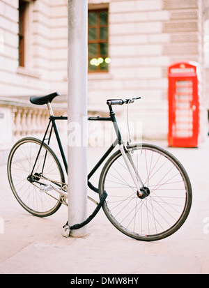 A bicycle chained and locked to a lamppost on a London street. A red public telephone box in  background. - Stock Photo