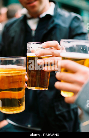 Three people drinking beer. Toasting each or. - Stock Photo