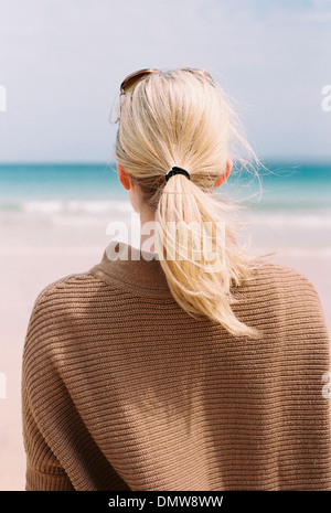 A blonde haired woman looking out to sea from  shore. - Stock Photo