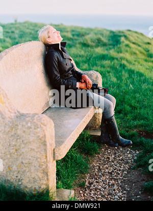 A woman seated on a stone bench on a coastal path. - Stock Photo