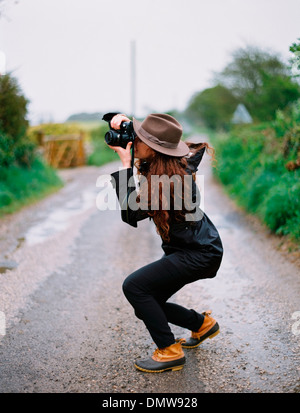 A woman crouching to take a photograph on a country road. - Stock Photo