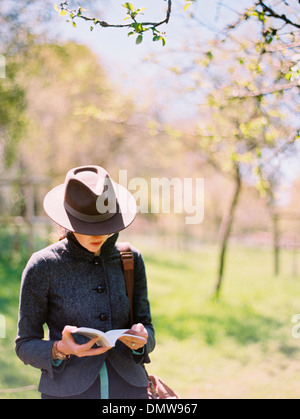A woman in a hat reading a book. - Stock Photo