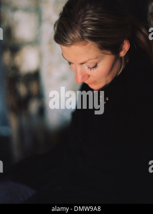 A woman wearing a black coat looking down in a pensive mood. - Stock Photo