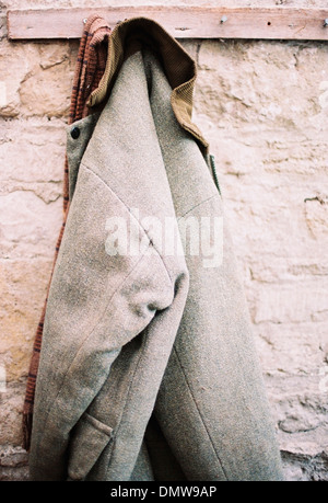 A traditional warm jacket with corduroy collar hanging from a pen on a stone wall. - Stock Photo