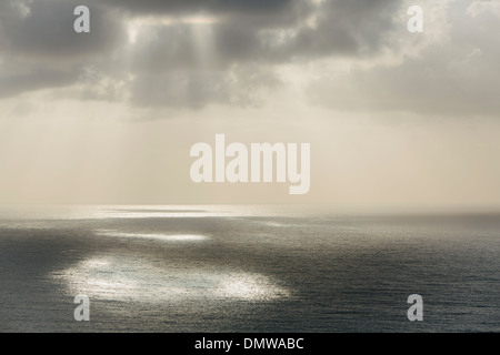 Shafts of sunlight shining through cloud and a view over  Pacific Ocean at Manzanita Oregon. - Stock Photo
