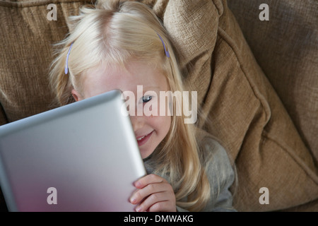 A young girl holding a silver laptop in front of her face. - Stock Photo