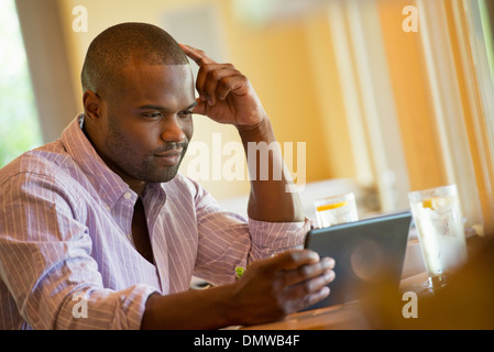 A man in a cafe using a digital tablet. - Stock Photo