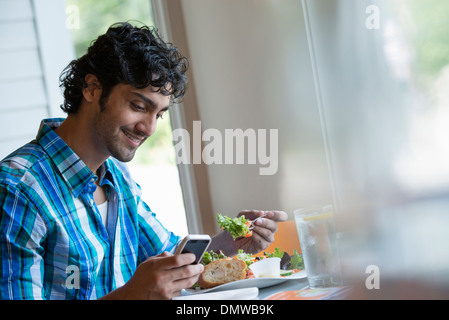 A  man seated checking his phone and eating in a cafe. - Stock Photo