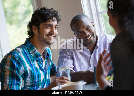 Three people seated at a table. - Stock Photo