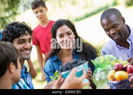 Adults and children around a table in a garden. - Stock Photo