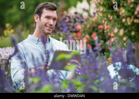 An organic flower plant nursery. A man working using a digital tablet. - Stock Photo