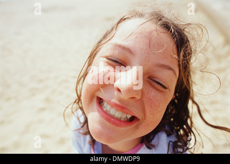 A young girl with a wide grin eyes half closed and wet hair outside in  rain. - Stock Photo