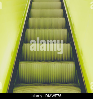 A flight of steps an escalator with a yellow painted border stripe on each side. - Stock Photo