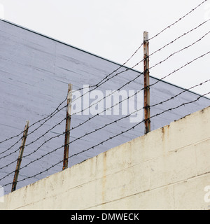 Barbed wire fence at  top of a wall in a city. - Stock Photo