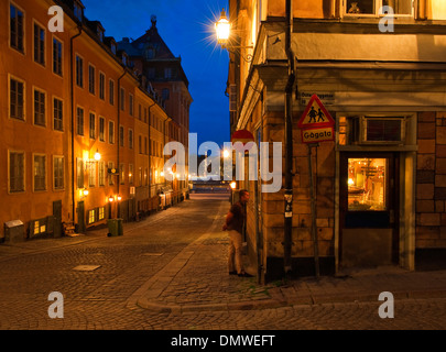 View down Brunnsgrand from Österlånggatan in Gamla Stan, the old town of Stockholm, Sweden.  A tourist looks in - Stock Photo