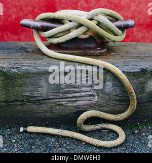 Close up of a wharfside mooring cleat with a fishing boat rope tied around it. - Stock Photo