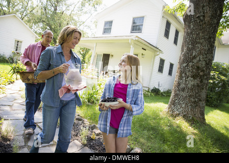 A family summer garing at a farm. Two adults and a young girl. - Stock Photo