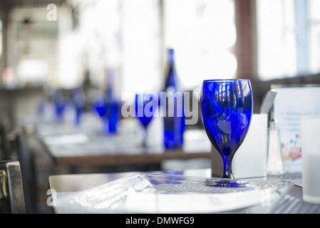 A cafe interior. Bright blue glassware on empty tables. - Stock Photo