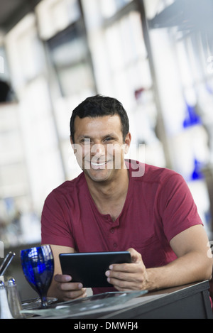 A cafe interior. A man sitting using a digital tablet. - Stock Photo