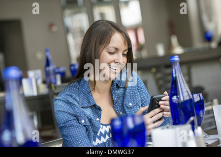 A woman seated in a cafe using a smart phone. - Stock Photo