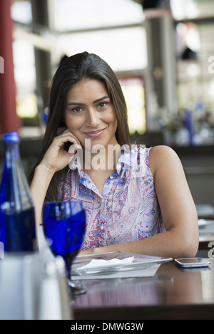 A cafe interior. A young woman relaxing at a table. - Stock Photo