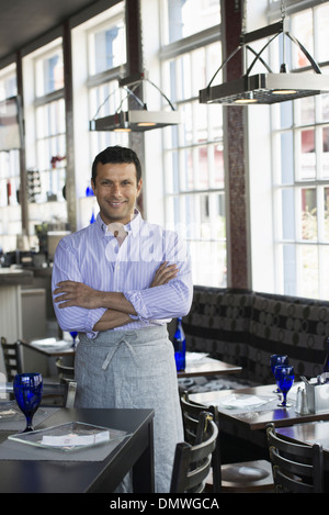 A cafe interior. A man in chef's whites. - Stock Photo