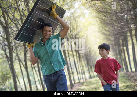 A man carrying a solar panel down an avenue of trees accompanied by a child. - Stock Photo