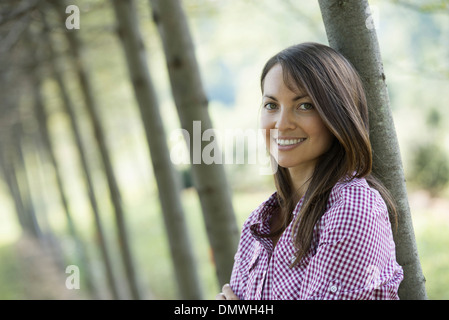 A woman  in an avenue of trees smiling. - Stock Photo
