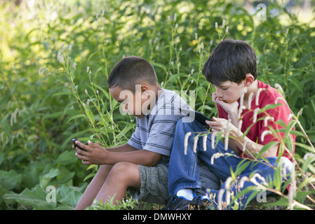 Two boys sitting in a field one on a smart phone and one using a digital tablet. - Stock Photo