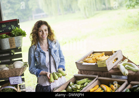 An organic fruit and vegetable farm. A young woman sorting vegetables. - Stock Photo