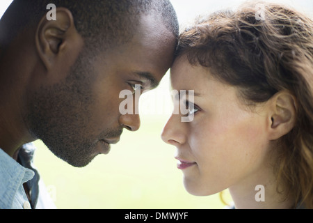 A young man and woman a couple. Touching foreheads viewed in profile. - Stock Photo