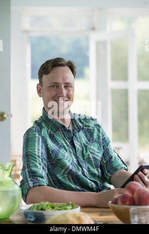 A man sitting at a table using a digital tablet. - Stock Photo