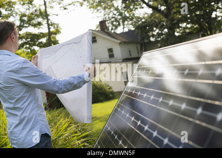 A man using a plan to place a solar panel in a farmhouse garden. - Stock Photo