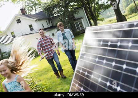 Two people walking towards a farmhouse garden. - Stock Photo