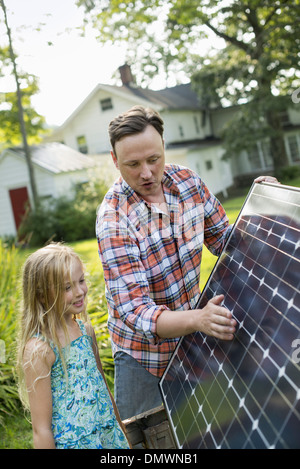 A man and a young girl looking at a solar panel in a garden. - Stock Photo