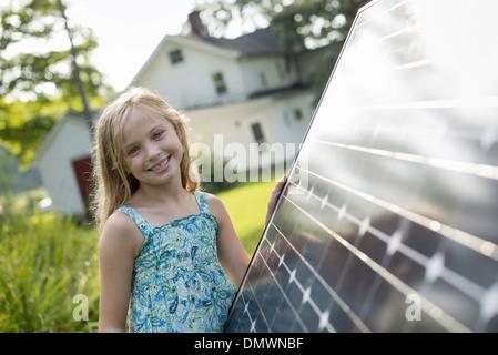 A young girl beside a large solar panel in a farmhouse garden. - Stock Photo