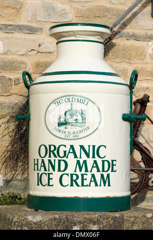An old milk churn painted to advertise ice cream at the Old Mill Lower Slaughter the Cotswolds UK - Stock Photo