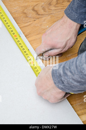 Male hands measuring and cutting gypsum plasterboard - Stock Photo