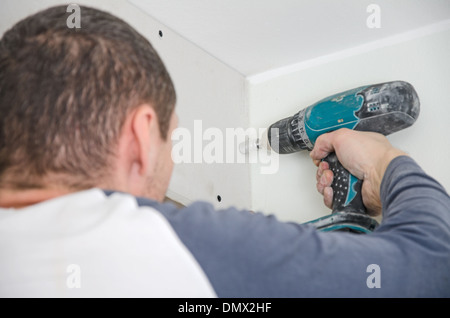 Builder mounting gypsum plasterboard frame on the wall - Stock Photo