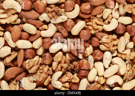 Peanuts, walnuts, almonds, hazelnuts and cashews forming a nuts background - Stock Photo