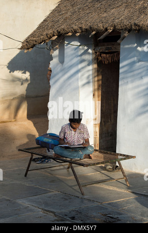 Young Indian boy doing school work outside his rural Indian village home. Andhra Pradesh, India - Stock Photo