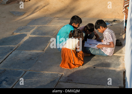 Young Indian boy doing school work outside his rural Indian village home. Andhra Pradesh, India. - Stock Photo